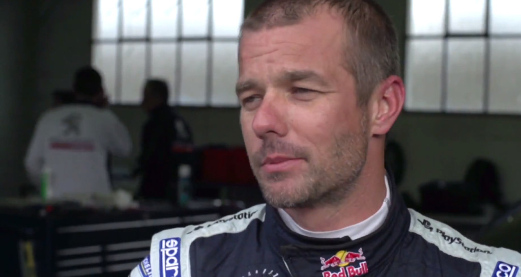 Sebastien Loeb suited up getting ready to test drive the PEUGEOT 208 T16 Pikes Peak [credit youtube.com/MagazineMotorsport]