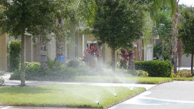 Grass getting watered by sprinkler system in the day in Kings Point developement in Sun City Center, FL/photonews247.com