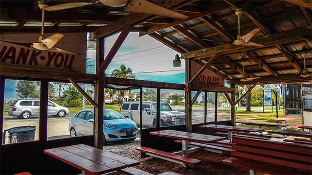 Park benches under pavilion at The Fish House outdoors fresh seafoof diner on Shell Point Road, Ruskin, FL