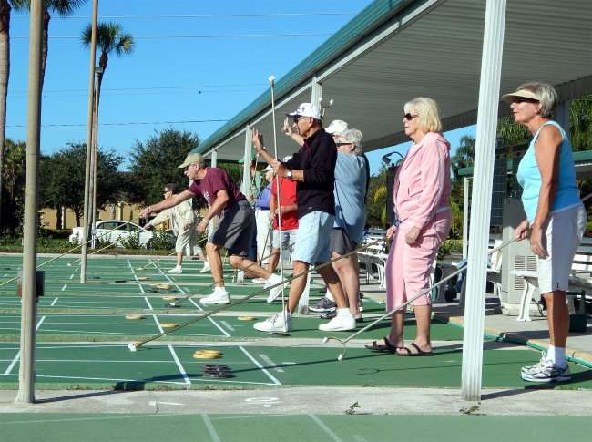 Showing points by holding up fingers in shuffleboard game in Kings Point, Sun City Center, FL/photonews247.com