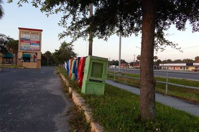 MAY 12, 2015: newspaper vending machines on grass at strip-mall on Us 41, Gibsonton South Shore, FL / Photo News 247