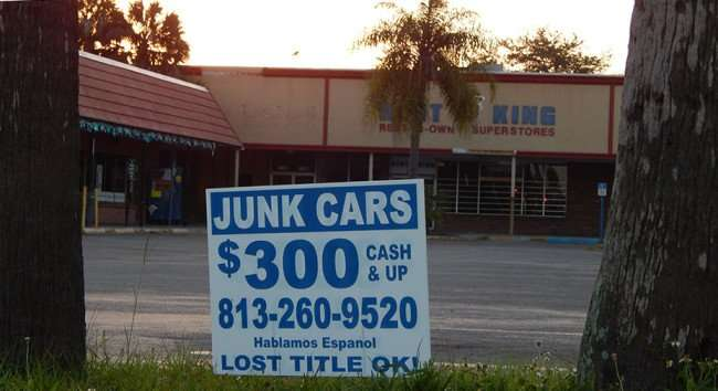MAY 12, 2015: sign JUNK CARS $300 LOST TITLE OK at Twin Oaks strip mall in Gibsonton South Shore, FL/ Photo News 247