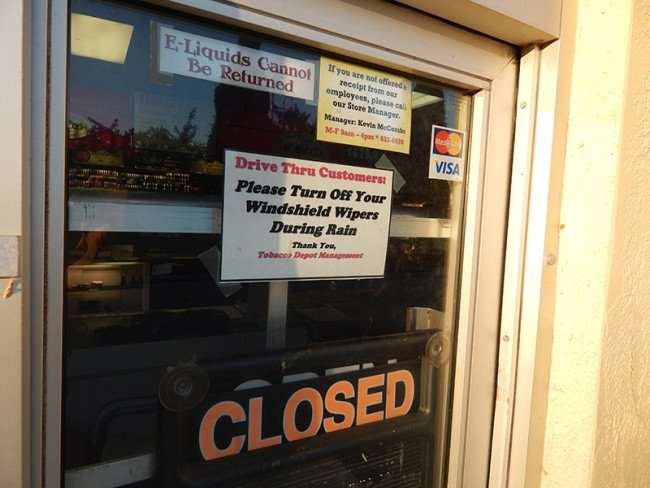 MAY 18, 2015 - Drive-thru window with closed sign hanging from glass at Tobacco Depot in retirement community in Sun City Center, FL