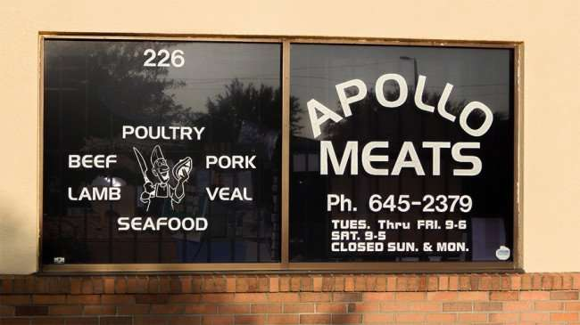 MAY 22, 2015 - Front window with hours for Apollo Meats in Apollo Beach, Florida