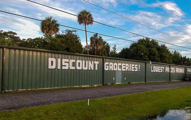 MAY 27, 2015 - Green building with Discount Grocery and Lowest Prices Around painted on front, Gibsonton, FL