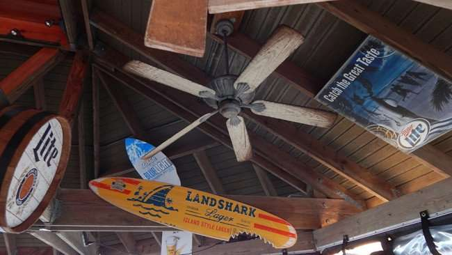 MAY 10, 2015: Sunset Tiki Bar with ceiling advertisments, Miller Lite, Bud Light, Landshark Lager surfboard with shark bite / Photo News 247