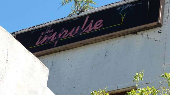THE IMPULSE bar sign hangs on 2nd floor on 15th street chard from the fire