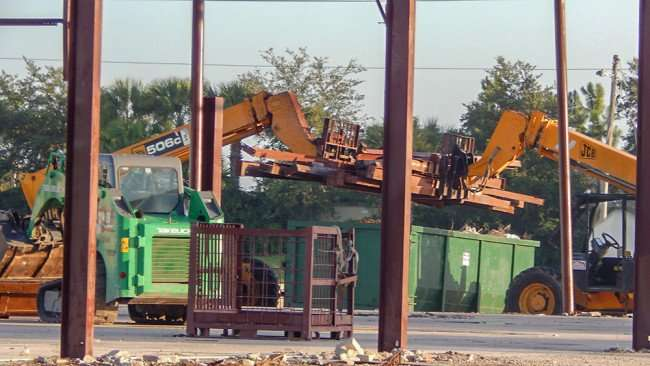 June 15, 2015 - tractors putting steel i-beams in oversized bin for hauling from Cox Lumber property in Apollo Beach, FL