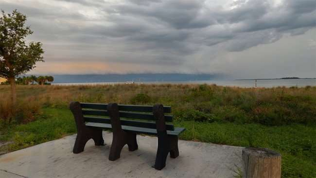 June 22, 2015 - Park bench looking out at beach at Apollo Beach Nature Park in SouthShore, FL
