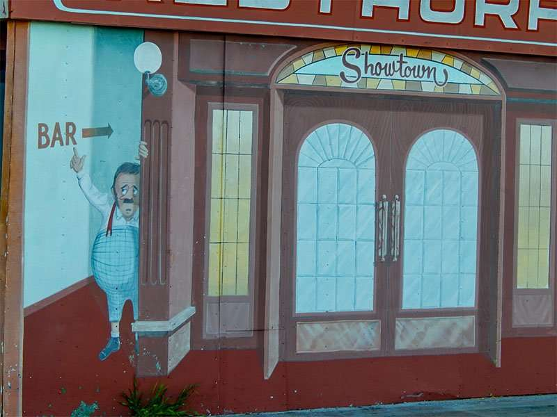MAY 31, 2015 - Animated painting of man pointing at bar sign in mural at Showtown USA, Gibsonton, FL
