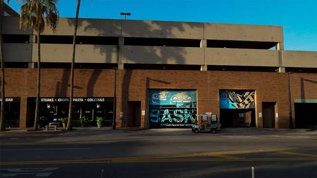 July 14, 2015 - Artists Tes One and BASK use Hyde Park Village dock rollup doors as canvas