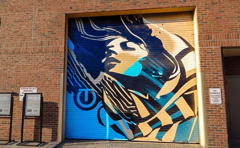July 19, 2015 - Artist Tes One use Hyde Park Village dock rollup doors as canvas