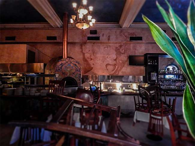 NOV 8, 2015 - Bernini Italian Restaurant inside with image of womens face on wall in Kitchen by wood burning store, Ybor City Tampa, FL/photonews247.com