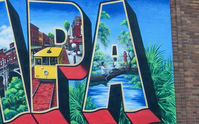 July 19, 2015 - City of Tampa Postcard with letter 'P' containing an Ybor street car by the RITZ and the letter 'A' with children fishing from a tree. painting by Carl Cowden III