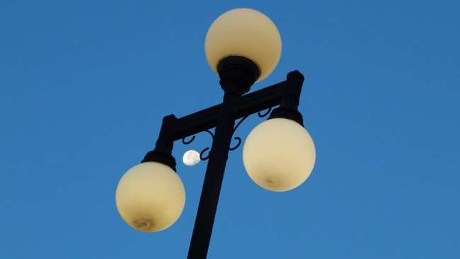 July 5, 2015 - Moon showing between street lights in Centro Ybor food court area in Tampa, FL