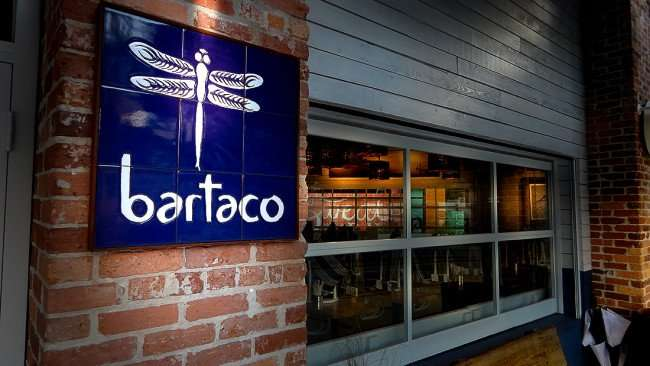 July 14, 2015 - bartaco sign with dragonfly logo next to front door in Hyde Park Village. Tampa, FL