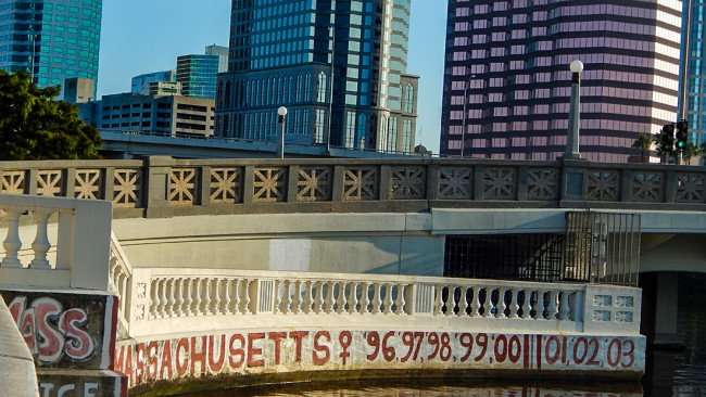 AUG 9, 2015 - Bayshore Walk with UT graffiti by Massachusetts Row Team on Platt St Bridge with buildings in background/photonews247.com
