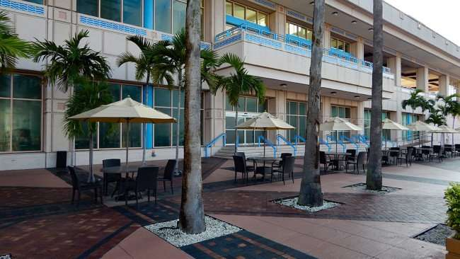 AUG 9, 2015 - Tampa Convention Center with tables with umbrellas on decorated bricked patio in the back/photonews247.com