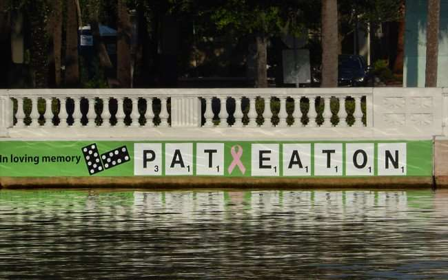 "AUG 9, 2015 - Memorial - ""In Loving Memory Pat Eaton"" with dominos and pink ribbon on Hillsborough River wall in Tampa, FL/photonews247.com"