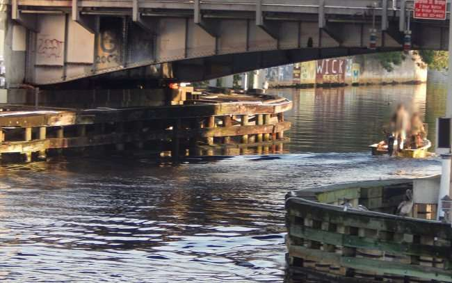 AUG 9, 2015 - Small fishing boat going under bridge on Hillsborough River with graffiti on bridge and sea wall, Tampa, FL/photonews247.com