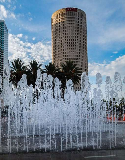 AUG 23, 2015 - Water fountains at water park with Rivergate Towers in background, Downtown Tampa, FL/photonews247.com