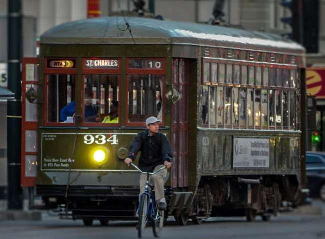 NOV 19, 2015 - Bicyclist riding on Canal Street in front of parked St Charles 934 Streetcar in New Orleans, LA/photonews247.com