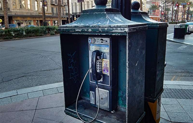 SEPT 13, 2015 - Green payphone booth attatched to street light pole on sidewalk along Canal Street in New Orleans/photonews247.com