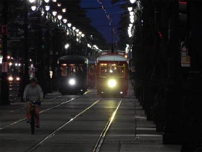 NOV 19, 2015 - Man on bike riding on Streetcar tracks with two streetcars behind him on Canal Street, New Orleans, LA/photonews247.com