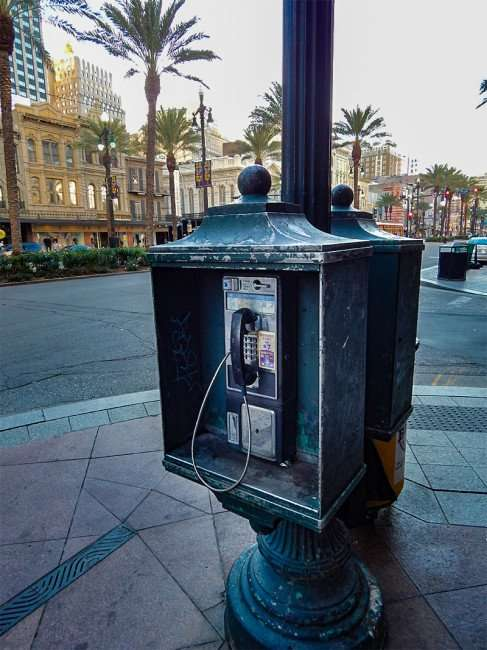 SEPT 13, 2015 - Phone booth on sidewalk along Canal Street in New Orleans, LA/photonews247.com
