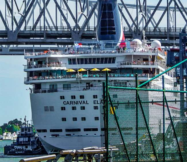 SEPT 14, 2015 - Tug boat secures Carnival Elation cruise ship docked on the Mississippi river in New Orleans, LA/photonews247.com