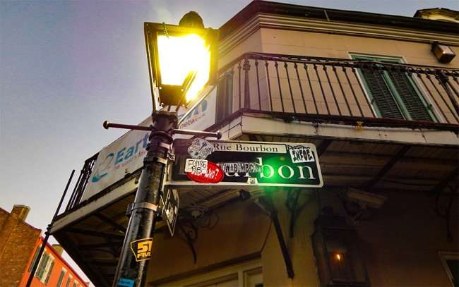 NOV 14, 2015 - decals and beads on lamp post at Bourbon Street and St Pete Street, New Orleans, LA/photonews247.com