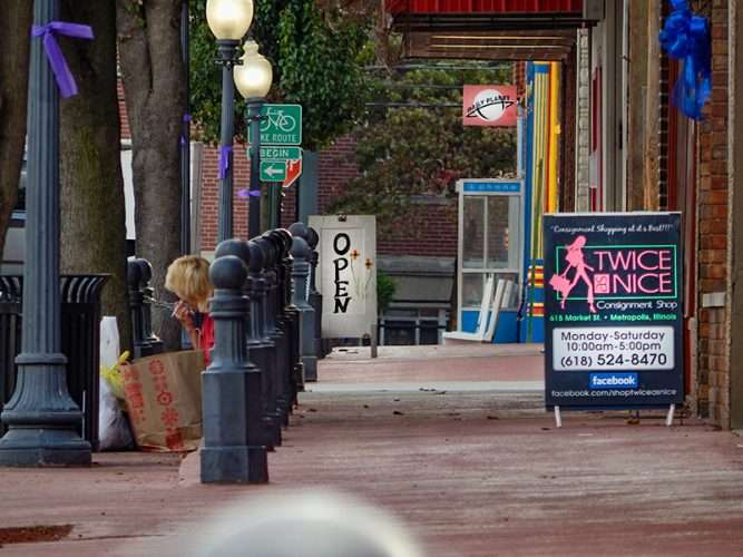 OCT 6, 2015 - A resident with her bags waits to be picked up after shopping on Market Street, Metropolis, Illinois/photonews247.com