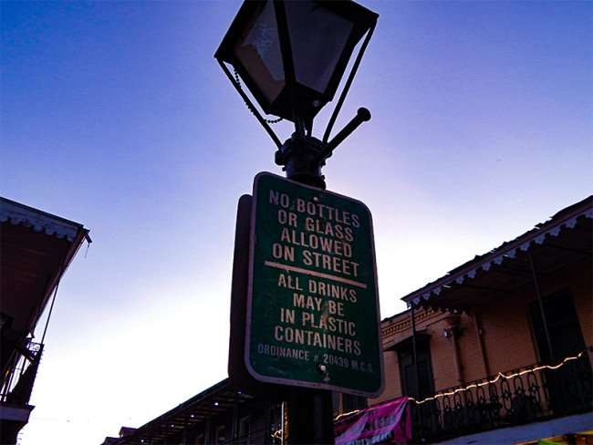 SEPT 14, 2015 - Beads hang from lamp post on Bourbon Street with NO GLASS IN STREET sign on Bourbon St, New Orleans, LA/photonews247.com