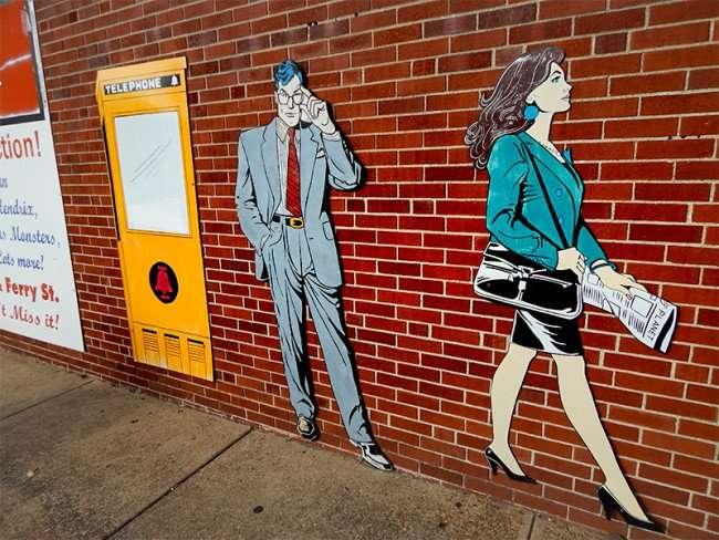 OCT 6, 2015 - Clark Kent watching woman walk by on sidewalk at Superman Museum, Metropolis, ILL/photonews247.com