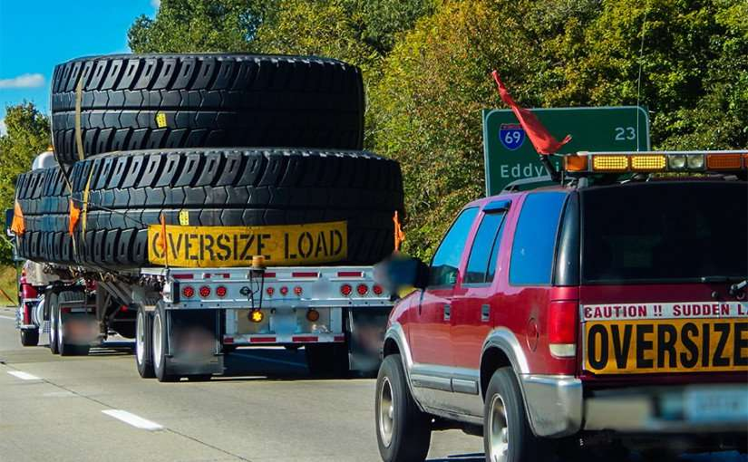 OCT 6, 2015 - Four giant tires on flatbed with OVERSIZE LOAD banner with caution car following behind with light behind/photonews247.com