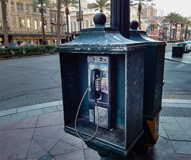SEPT 14, 2015 - Green payphone booth attatched to street light pole on sidewalk along Canal Street in New Orleans/photonews247.com