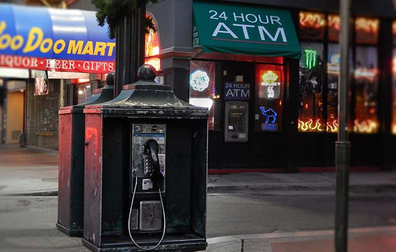 NOV 19, 2015 - Green payphone booth next to convenience store and ATM on Canal Street in New Orleans, LA/photonews247.com