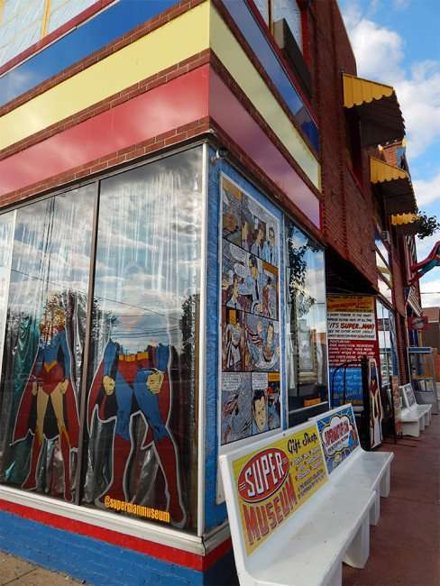 OCT 6, 2015 - Superman comics on window above sidewalk benches labeled with Superman ads at Superman Museum in Metropolis/photonews247.com