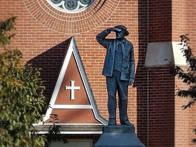 OCT 10, 2015 - A Memorial Statue of Man looking constructed in 1915 'with plate below that reads In Memory Of The First Settlers Of The Swiss Colony New Glarus Aug 16, 1845