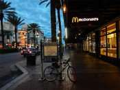 NOV 19, 2015 - McDonald's Restaurant with street guide on sign and palm trees along sidewalk on Canal Street, New Orleans, LA/photonews247.com