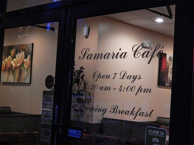NOV 15, 2015 - Samaria Cafe Restaurant front glass door with hours stenciled on window in Tampa, FL/photonews247.com
