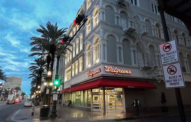 NOV 19, 2015 - Worker waters down sidewalk with hose at Walgreens on 801 Canal St, New Orleans, LA/photonews247.com