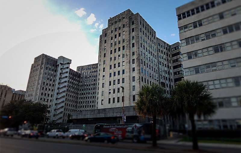 NOV 19, 2015 - Charity Hospital grey concrete building with dark stains and weathering on Tulane Ave, New Orleans, LA/photonews247.com