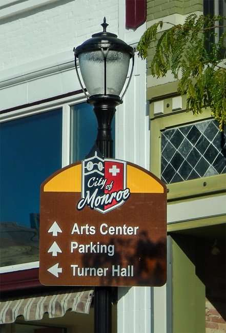 OCT 10, 2015 - City of Monroe sign with arrows pointing to Arts Center, Parking and Turner Hall, Monroe, WI/photonews247.com
