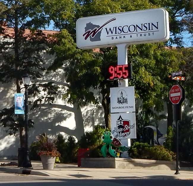OCT 10, 2015 - Main Street Monroe (aka 17th Ave) sign with turtle stature under Wisconsin Bank sign on the corner of 17th Avenue and 10th Street in Monroe, WI/photonews247.com