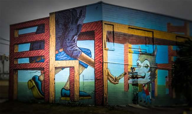 Jan 31, 2016 - Mural of evil giant feeding 24K gold scraps to severed dog's head held up by villagers in plan to get their stolen gold back in the Edge District neighborhood in St. Petersburg, FL/photonews247.com