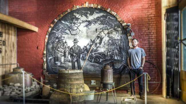 Aug 3, 2017 - Shanden Simmons next to his first mural created 2015in Moonshine Distillery atPaducah Distilled Spirits/photonews247.com