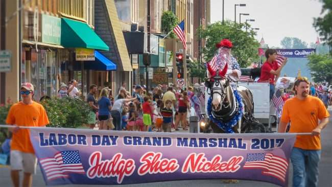 "Sept 4, 2017 - Two young men hold banner that reads ""Labor Day Grand Marshall Judge Shea Nickell"" during the Labor Day Parade. Judge Nickell is not visible in this photo but he's in the horse and carriage provided by John's Pass Carriage Service/photonews247.com"