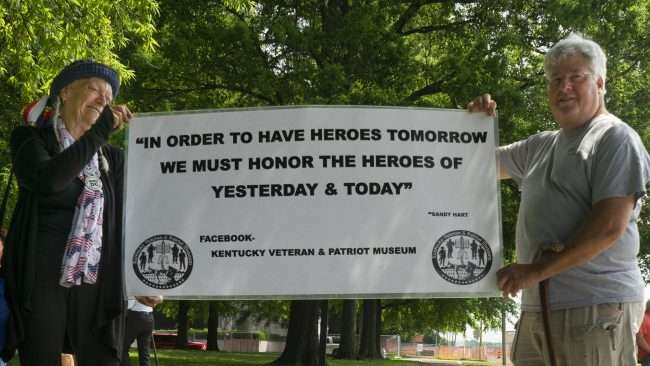 May 28, 2018 - Sandy & Bob Dwyer holds up banner for Patriot Museum after Global War on Terrorism Monument Ceremony in Padudah in honor of MSGT. Aaron C. Torian and Marine SGT Helfin and all other who have served/photonews247.com