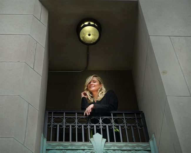 Courtney Tharpe on balcony at The Last Hotel in St. Louis. credit craig currie